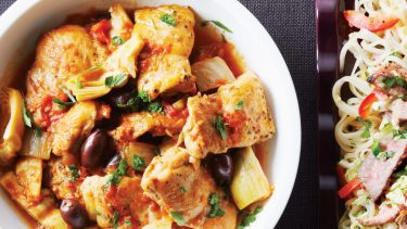 bowl of chicken thighs with olives and artichoke in a tomato sauce