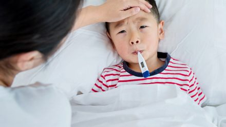 Kid lays in bed with a thermometer in his mouth while his mom holds a hand to his forehead