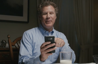 Will Ferrell looking at his cell phone at the dinner table