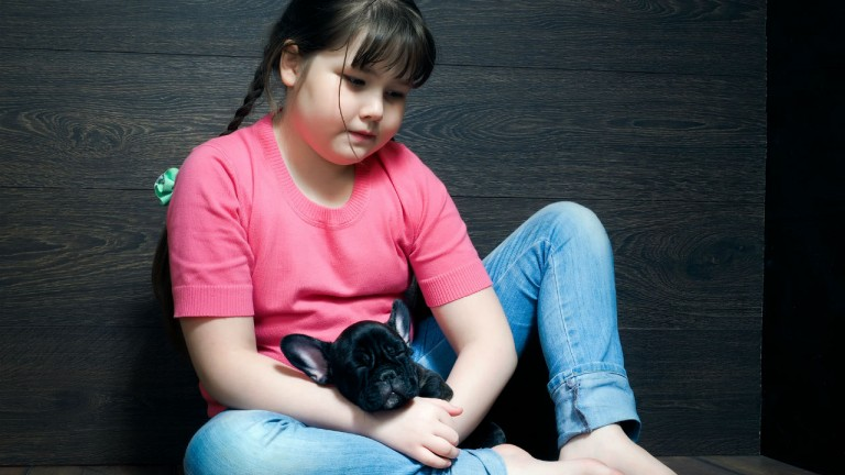 Girl sitting with her puppy looking sad