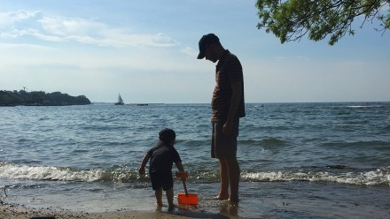 Dad looks over his son as they stand in the waves at the lakeshore. the son is digging into the sand with a red shovel