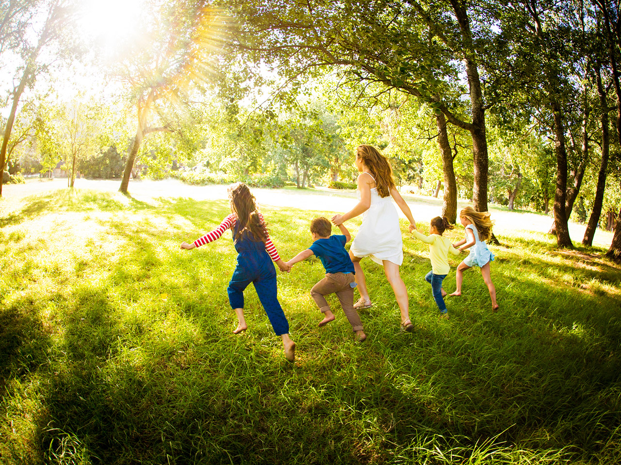 Family with four kids running through a field