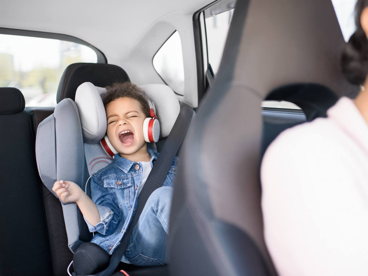 A little boy singing in the backseat of a car