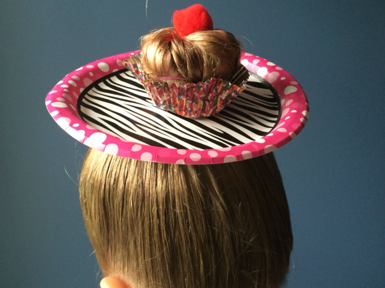 Paper plate with hair bun coming through to make it look like a cupcake on a plate
