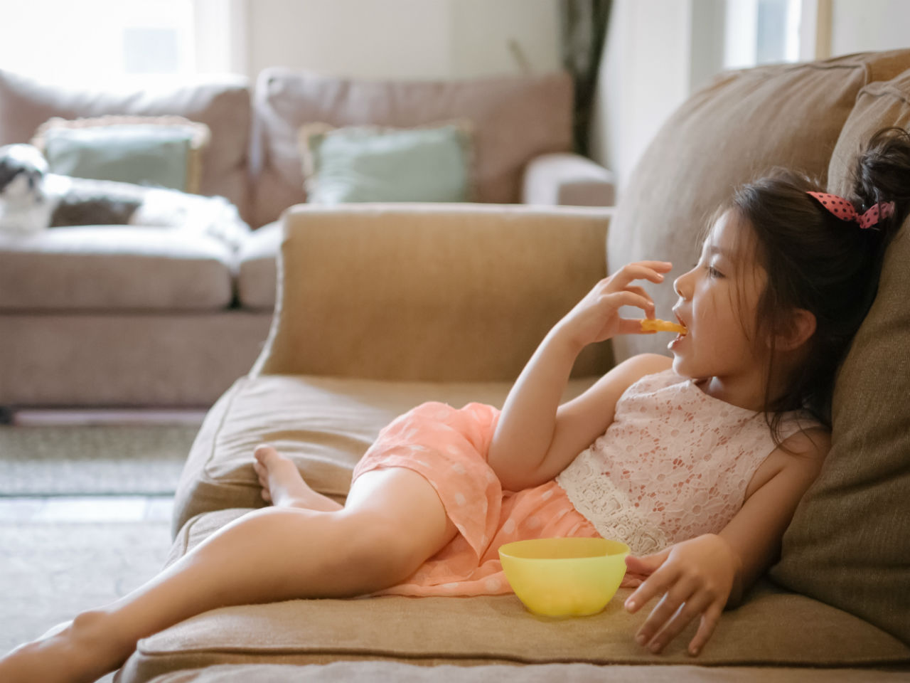 Little girl watching TV and eating chips