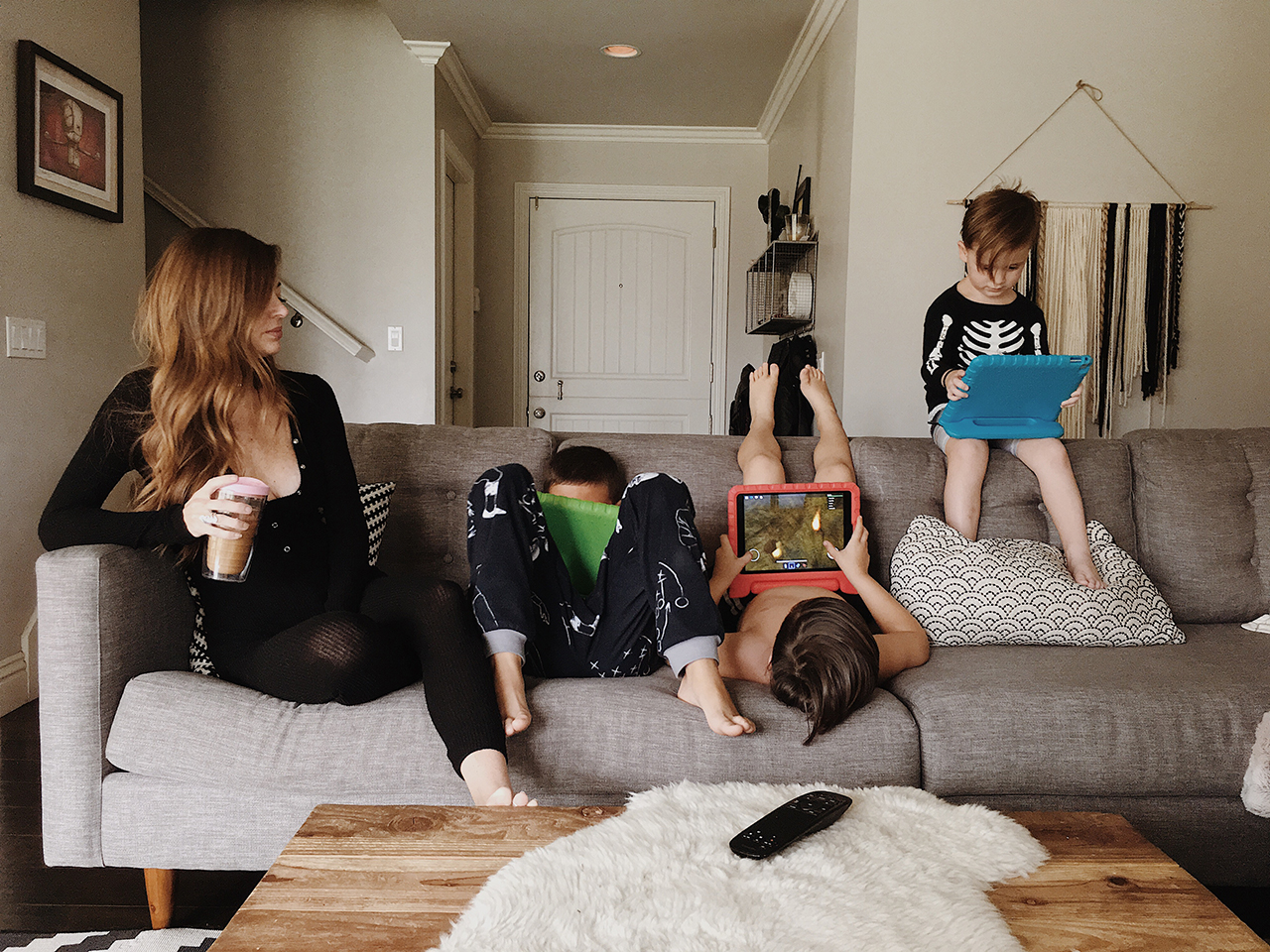 A mom surrounded by three kids on their iPads, enjoying their screen time