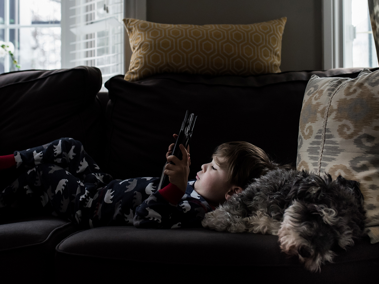 Child lying on the couch with his dog while on his iPad