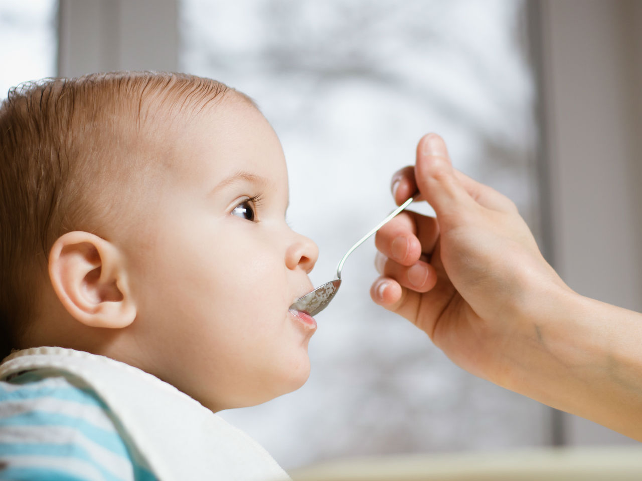 Baby being fed cereal with a spoon