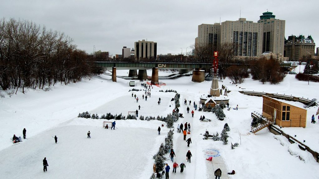 Skaters on a canal with CN bridge running overtop