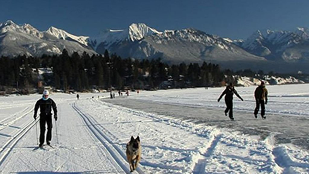 People skiing and skating in foothills of Rocky Mountains