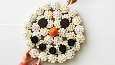 snowman made from cupcakes formed into a circle covered with mini marshmallows with cookie eyes and mouth and an ice cream cone nose