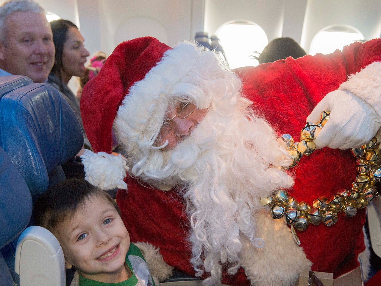 Santa taking a picture with a kid on an airplane
