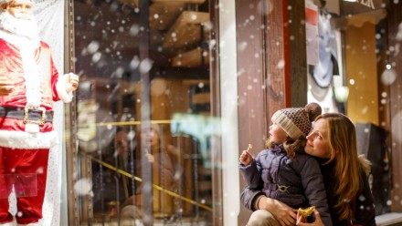 A mother and her daughter stare at a Santa Claus statue in a store window display.