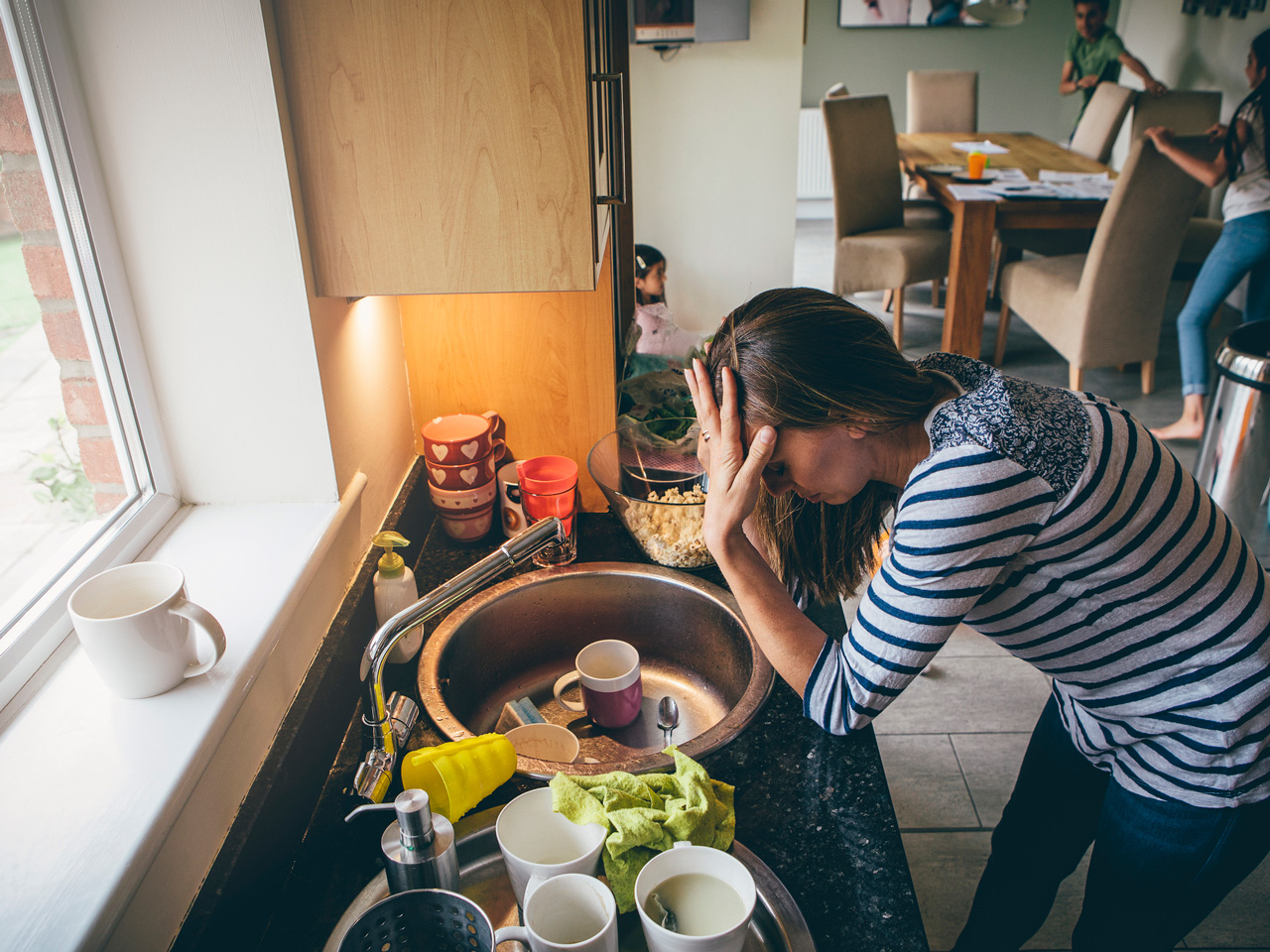 Mom leaning over messy counter looking very stressed as kids run around in background