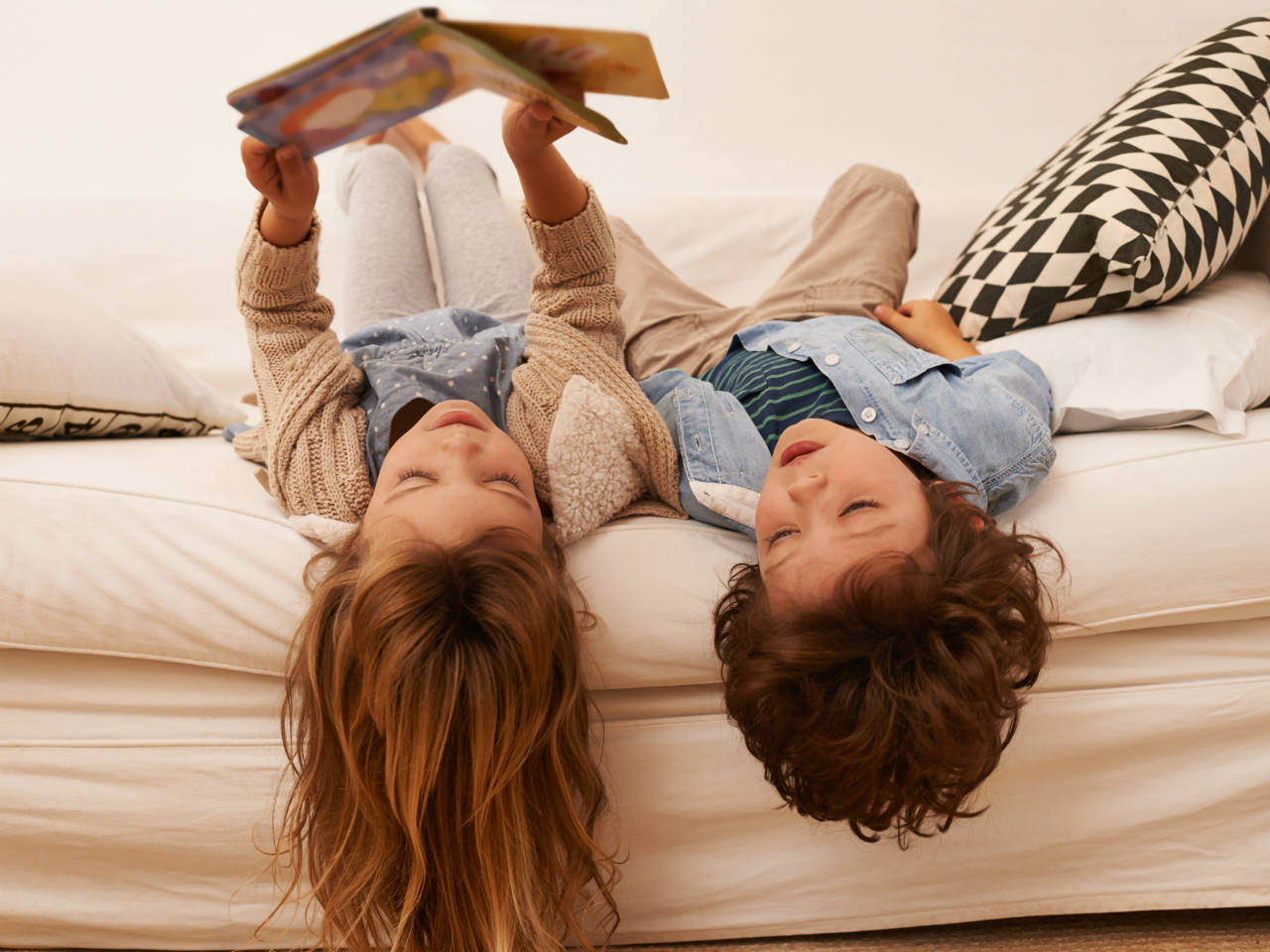 Two kids sitting upside down on the couch reading