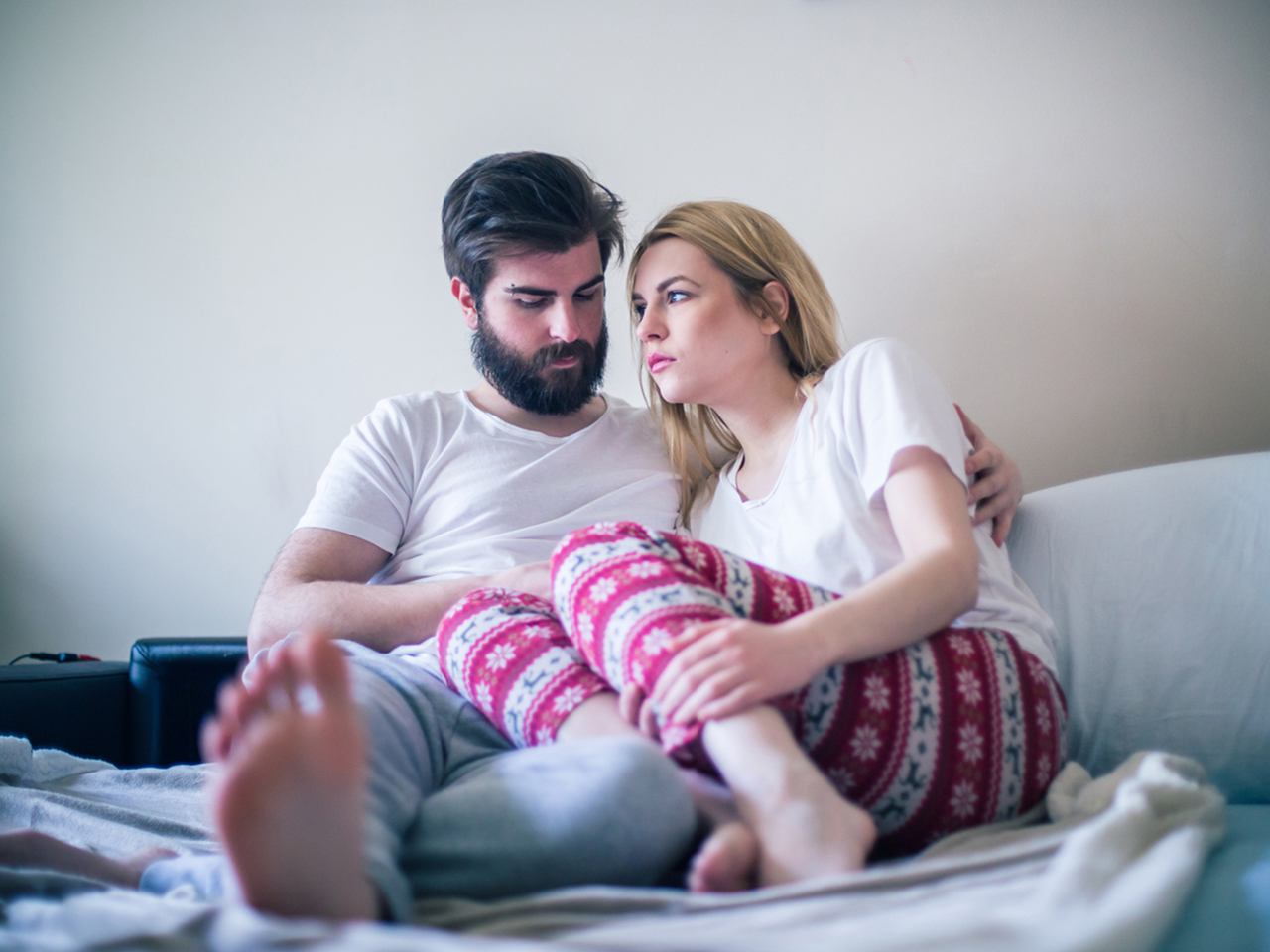 Young couple in bed looking worried