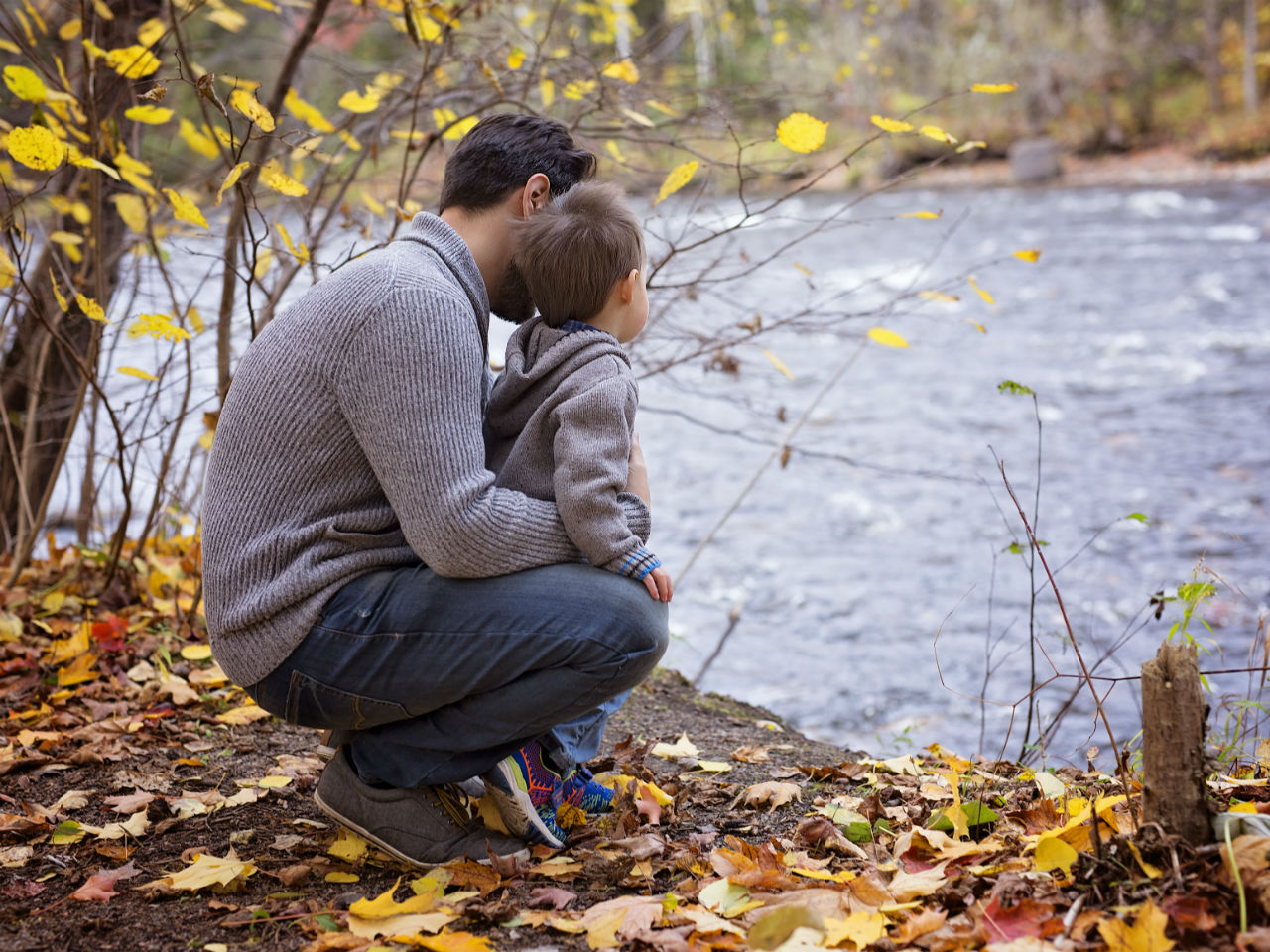 Dad looking at the water with his little boy