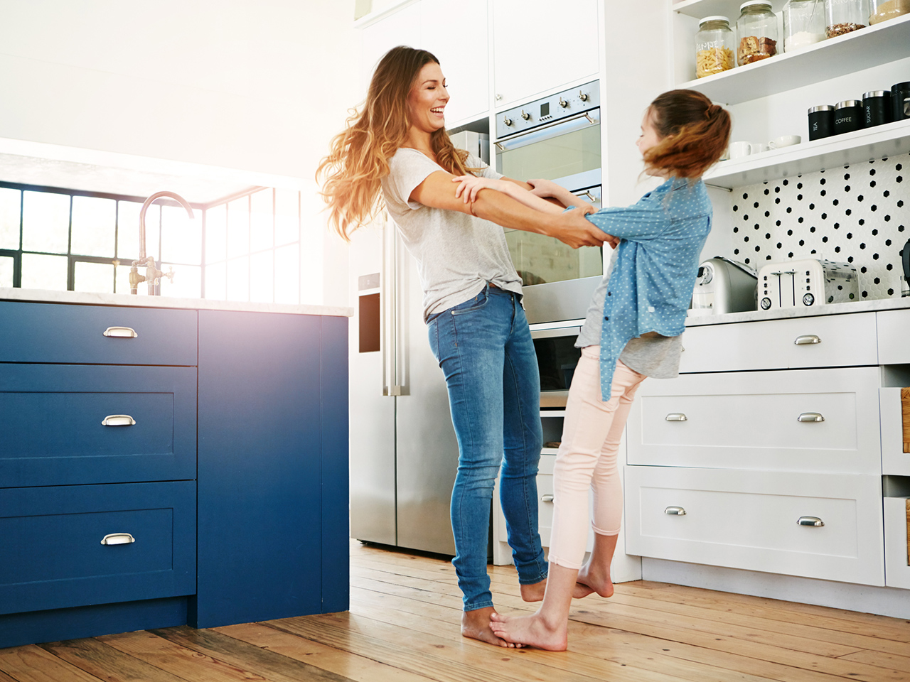 a happy mother and her daughter playfully dancing together at home