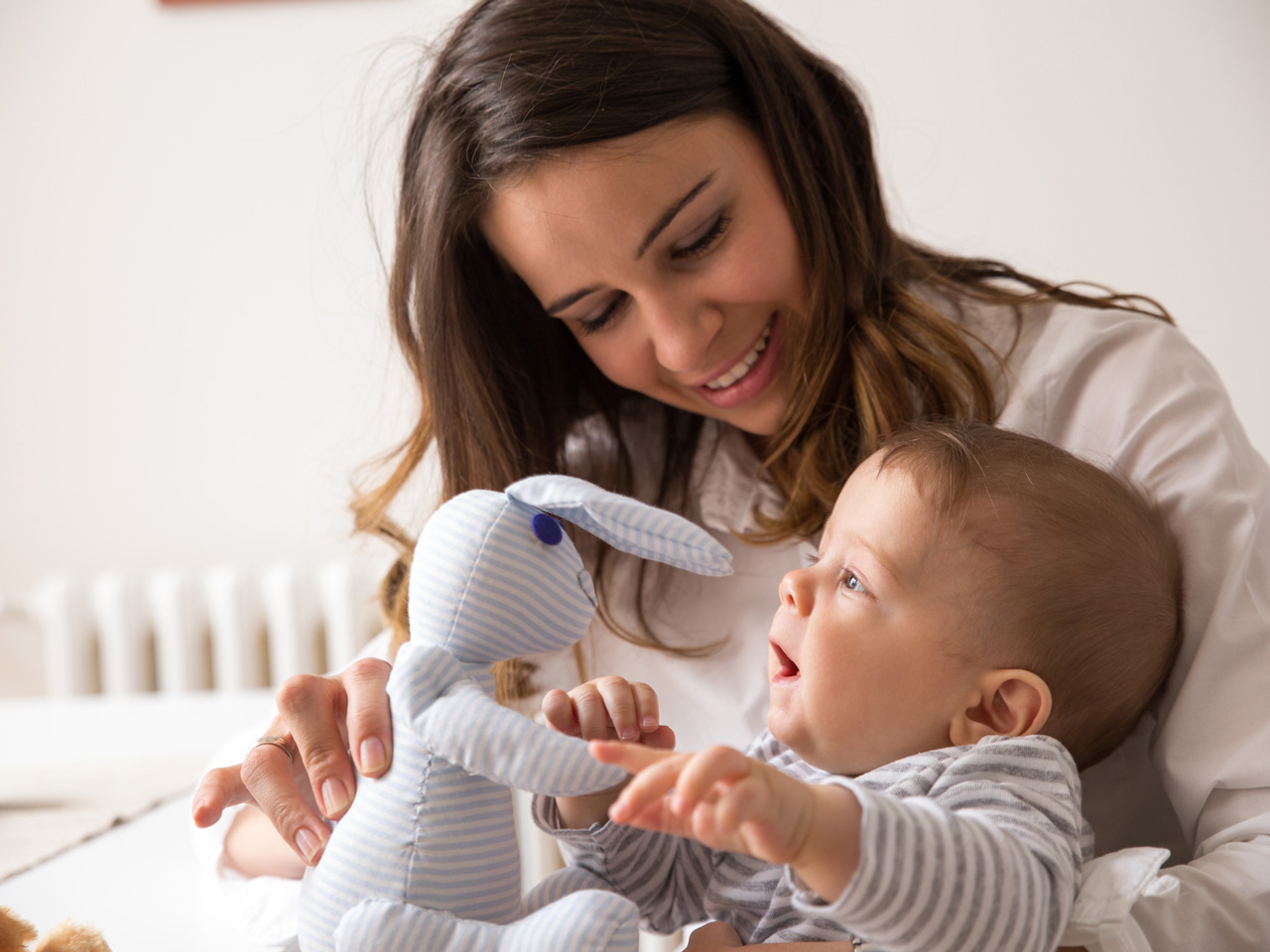 Woman holding her baby and putting a stuffed rabbit to his face