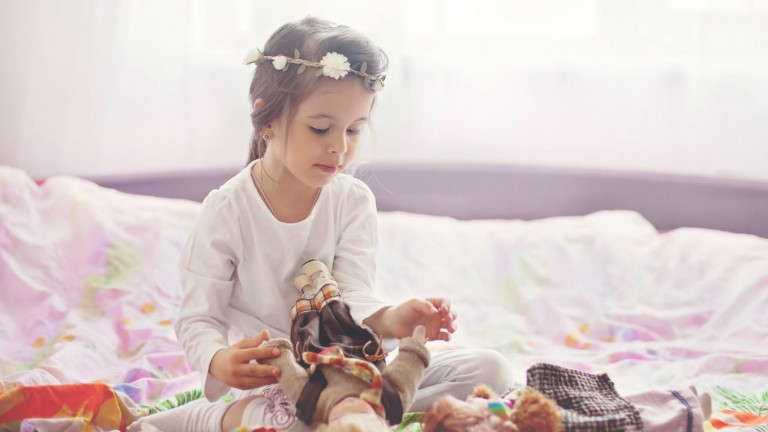 A little girl sitting on a bed playing with dolls