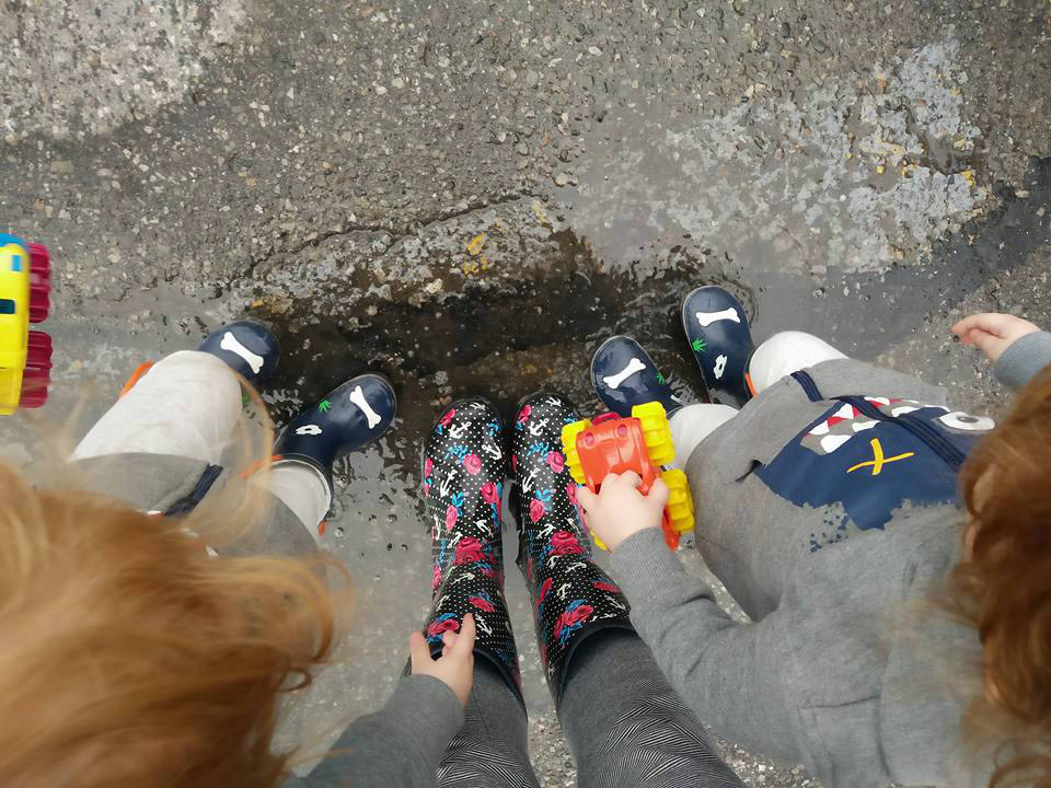 A bunch of little kids in rain boots on wet pavement