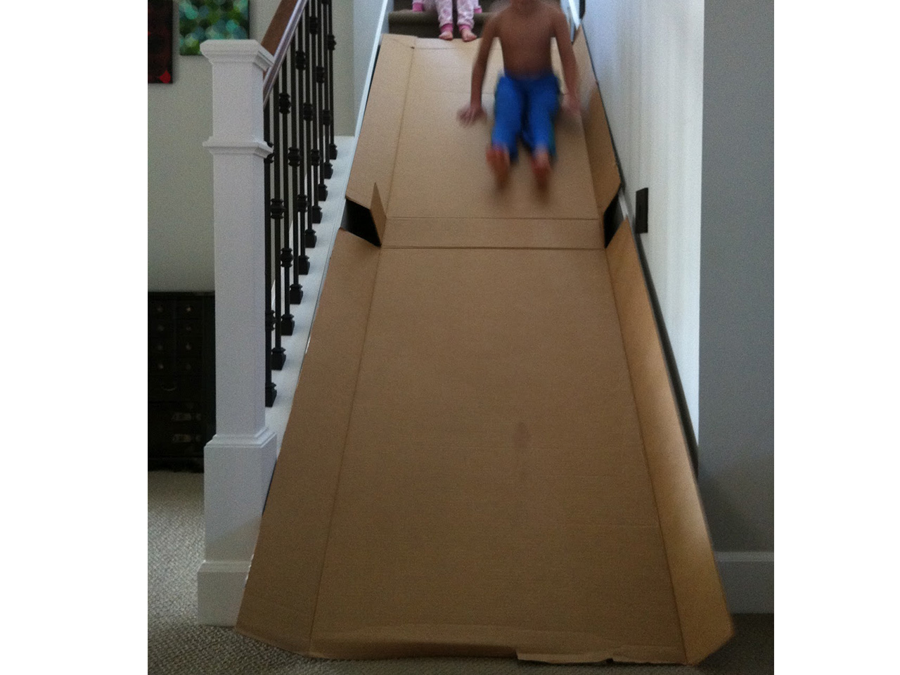 Kids going down a homemade cardboard slide on the stairs