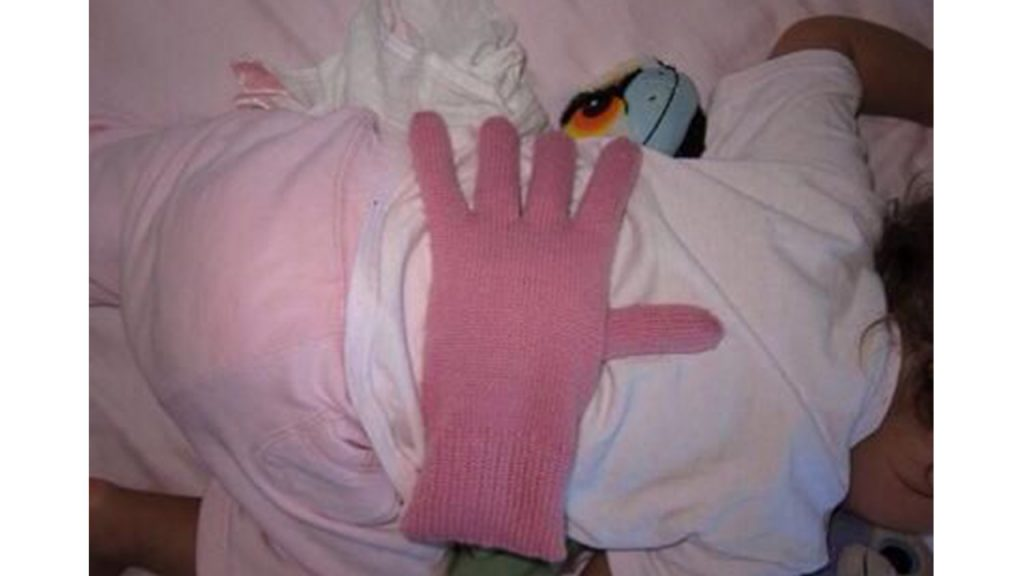 Baby sleeping with glove filled with beans on their back