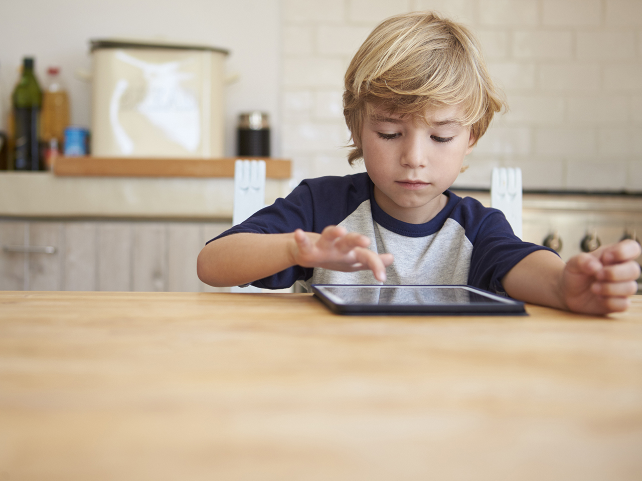 Young boy using tablet computer at kitchen table