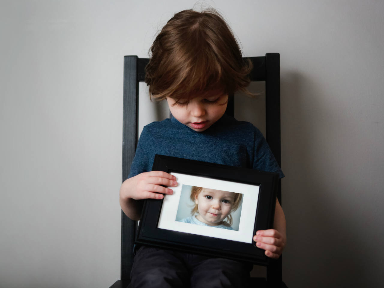 A little boy holding a picture of another boy
