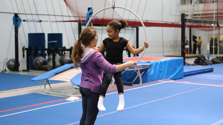 A girl helps her friend balance in a hanging hoop