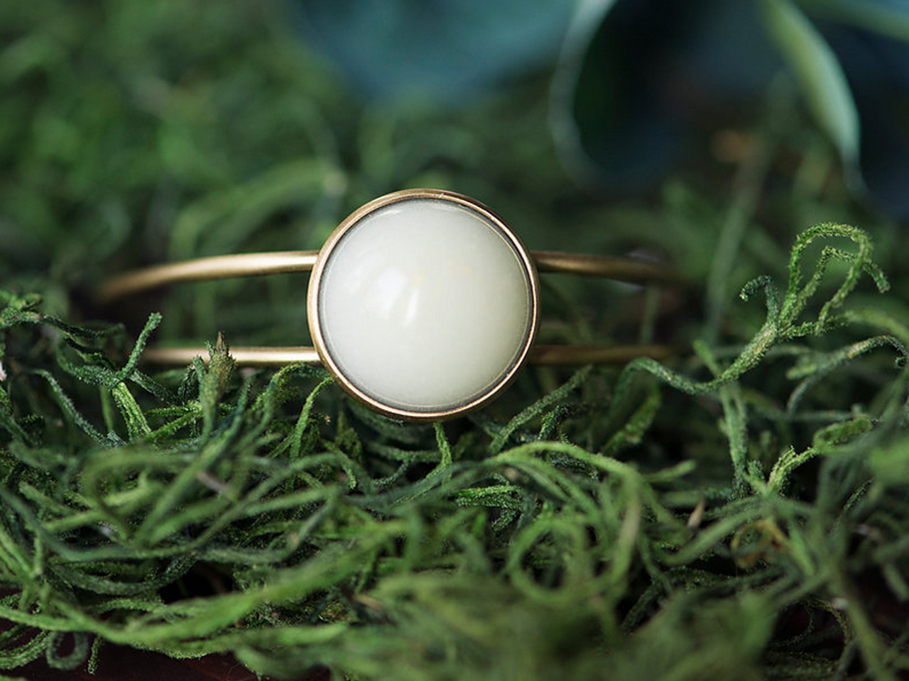 Bronze cuff bracelet with white opaque stone in the middle