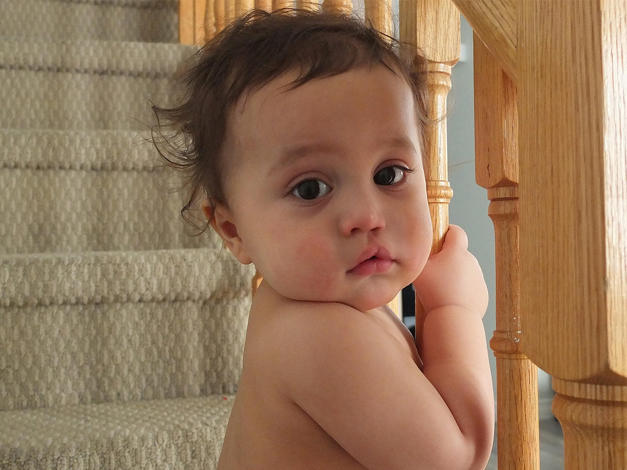 A toddler holds a bannister and looks at the camera