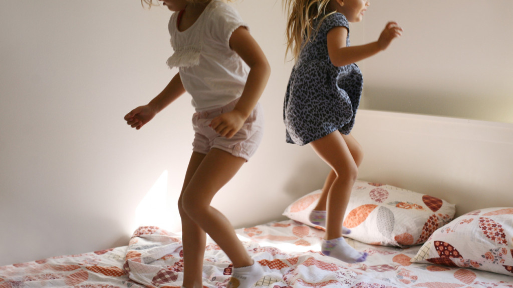 Two little girls jumping on a bed