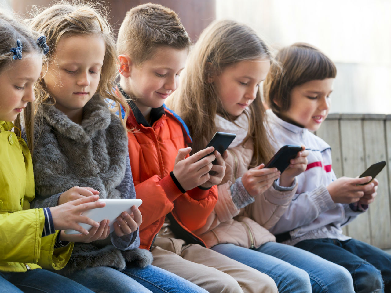 A group of kids on smartphones and iPad
