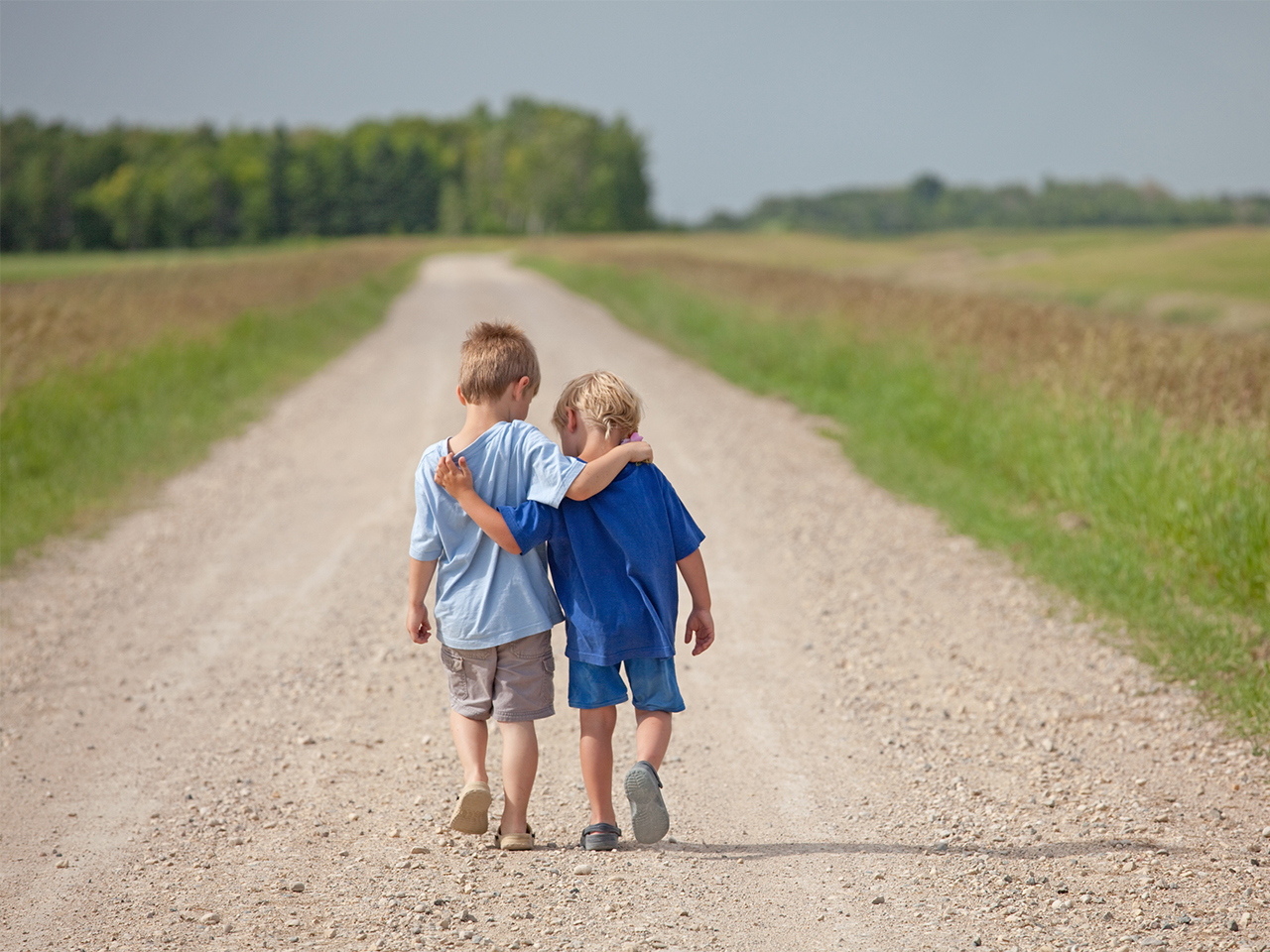 Two little boys walk down a country road with their arms around each other