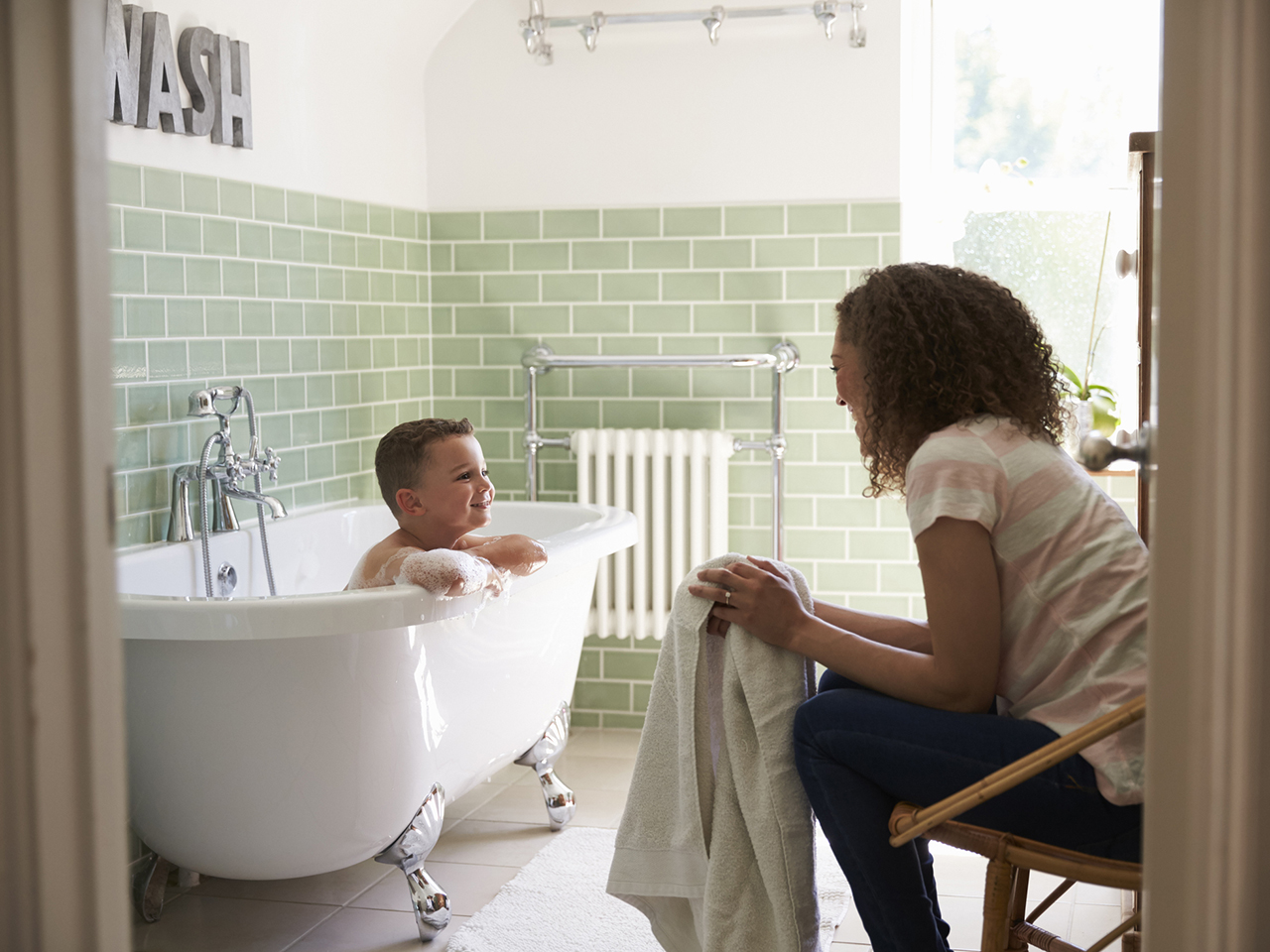 Son in the bath tub for bath time with his mom sitting down with a towel