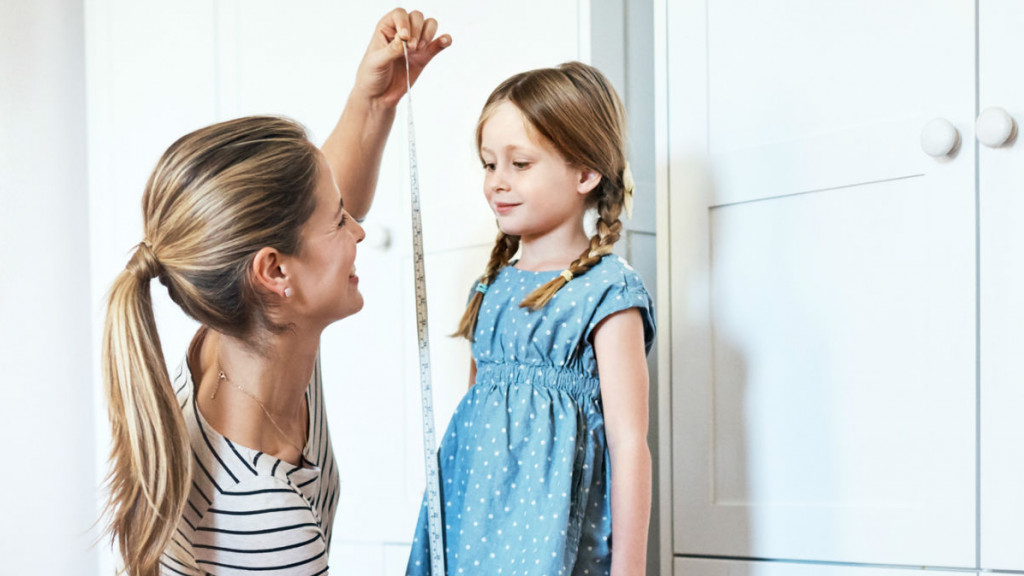 A mom measures her daughter's height