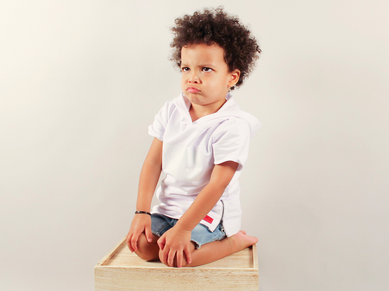 A young boy pouts as he kneels on a crate