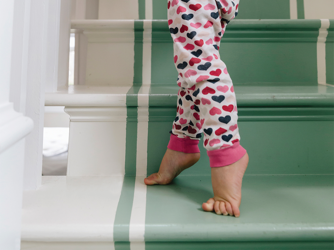 A toddler walks up stairs on her tiptoes