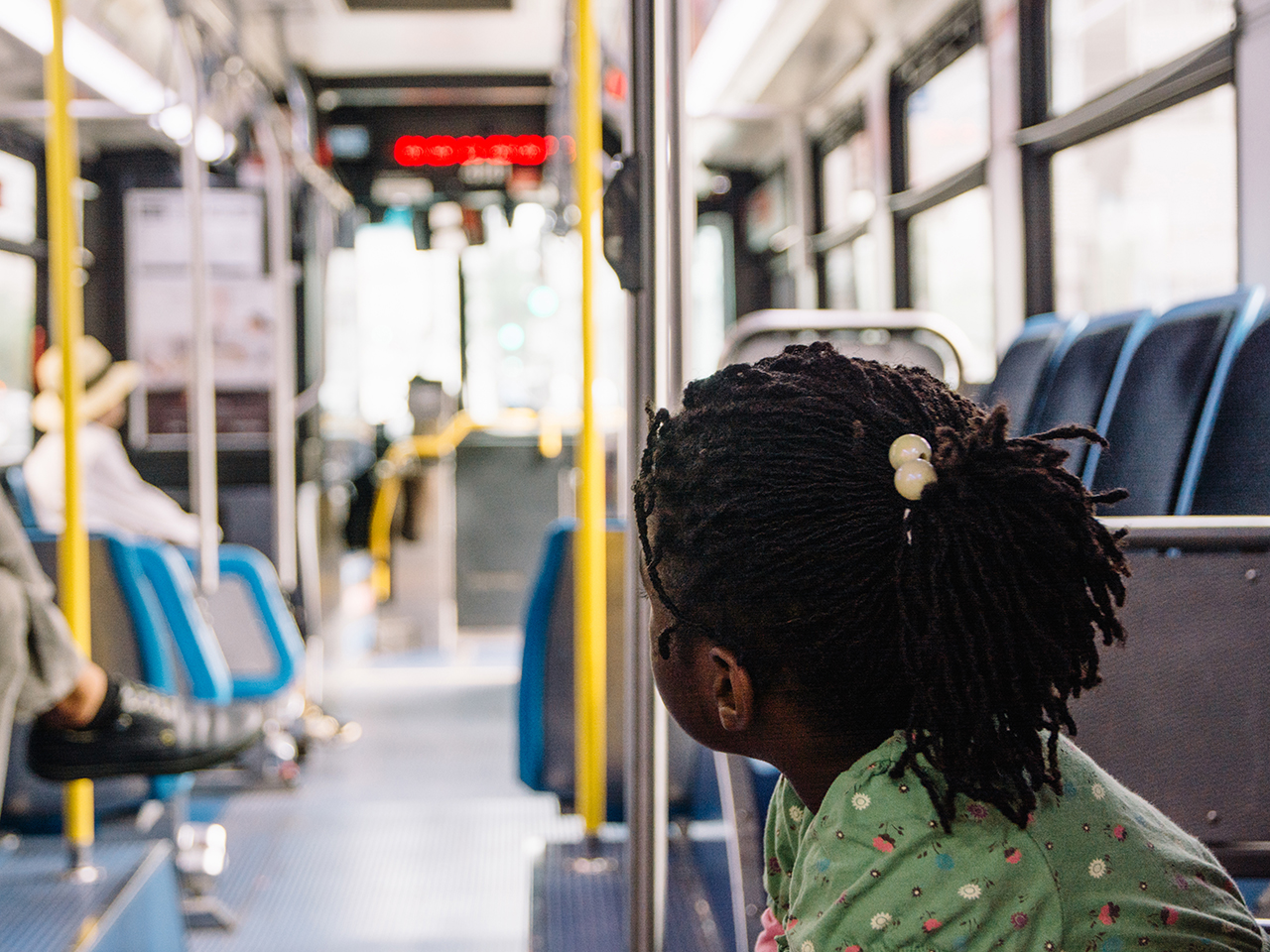 African American girl inside a bus in a city.