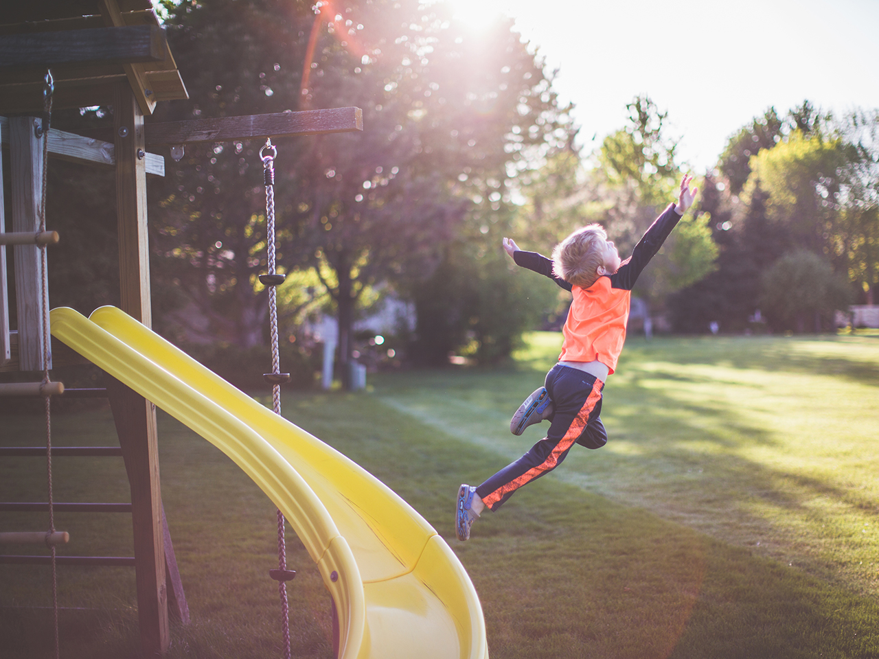 Little boy flies through the air as he jumps off the side of a backyard jungle gym slide onto a sun dappled lawn.