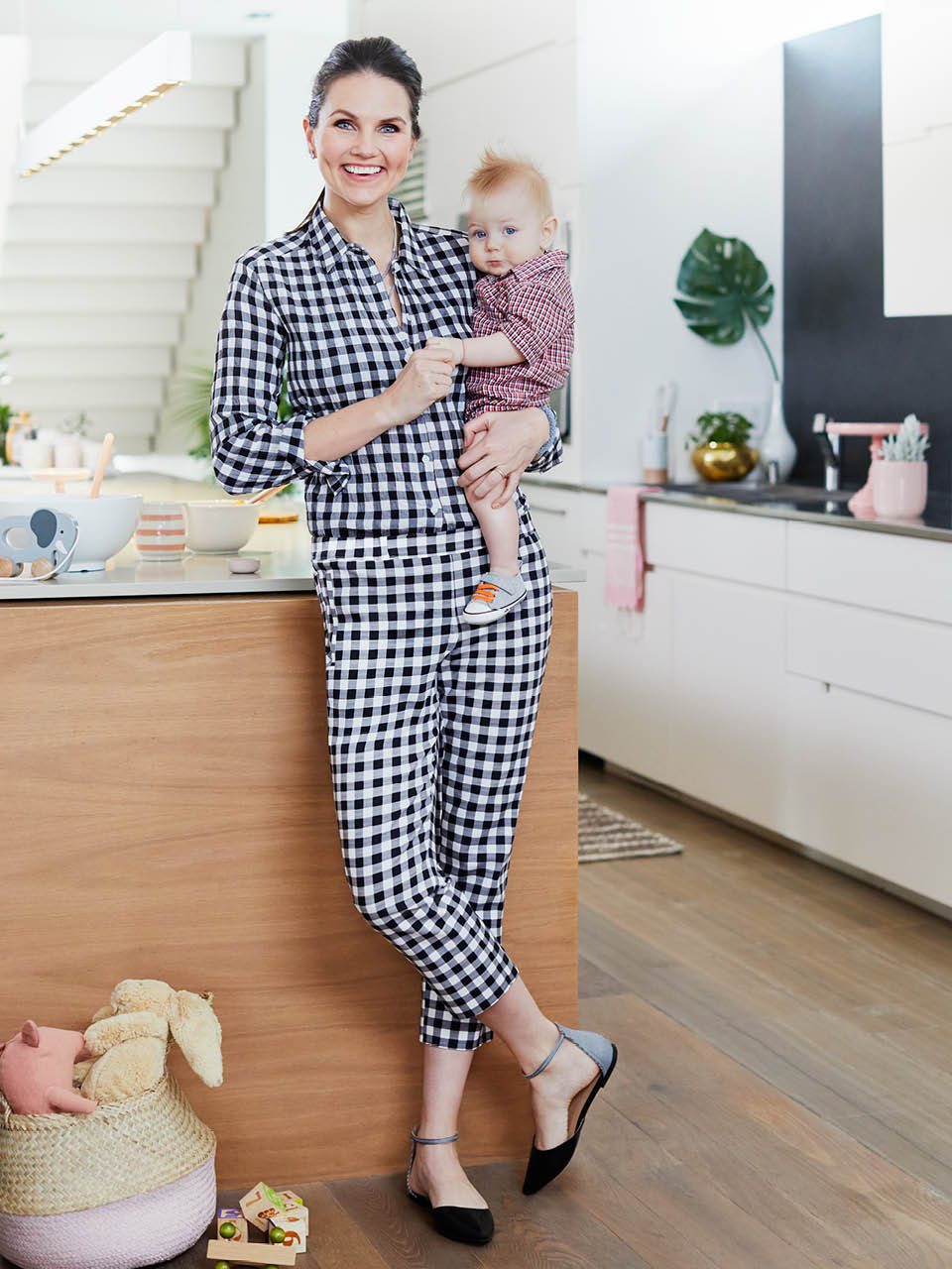 Mom wearing all gingham in kitchen holding her baby