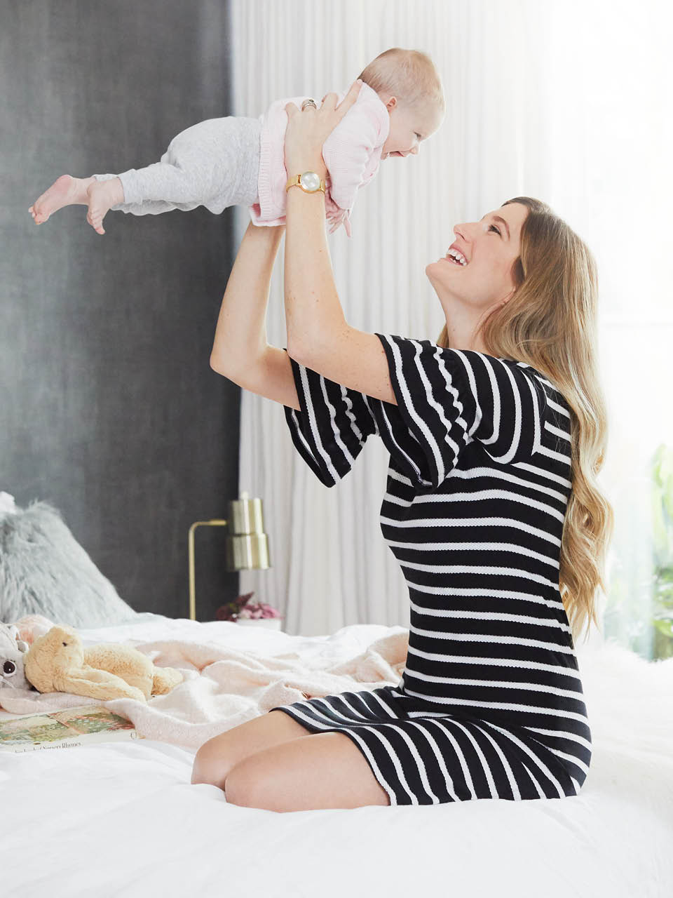 Mom in a striped dress sitting on bed holding a baby above her head