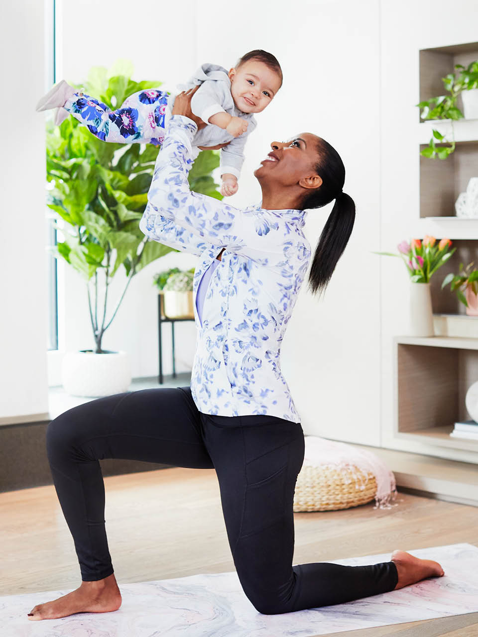 Mom in workout wear holding up baby while in a lunge