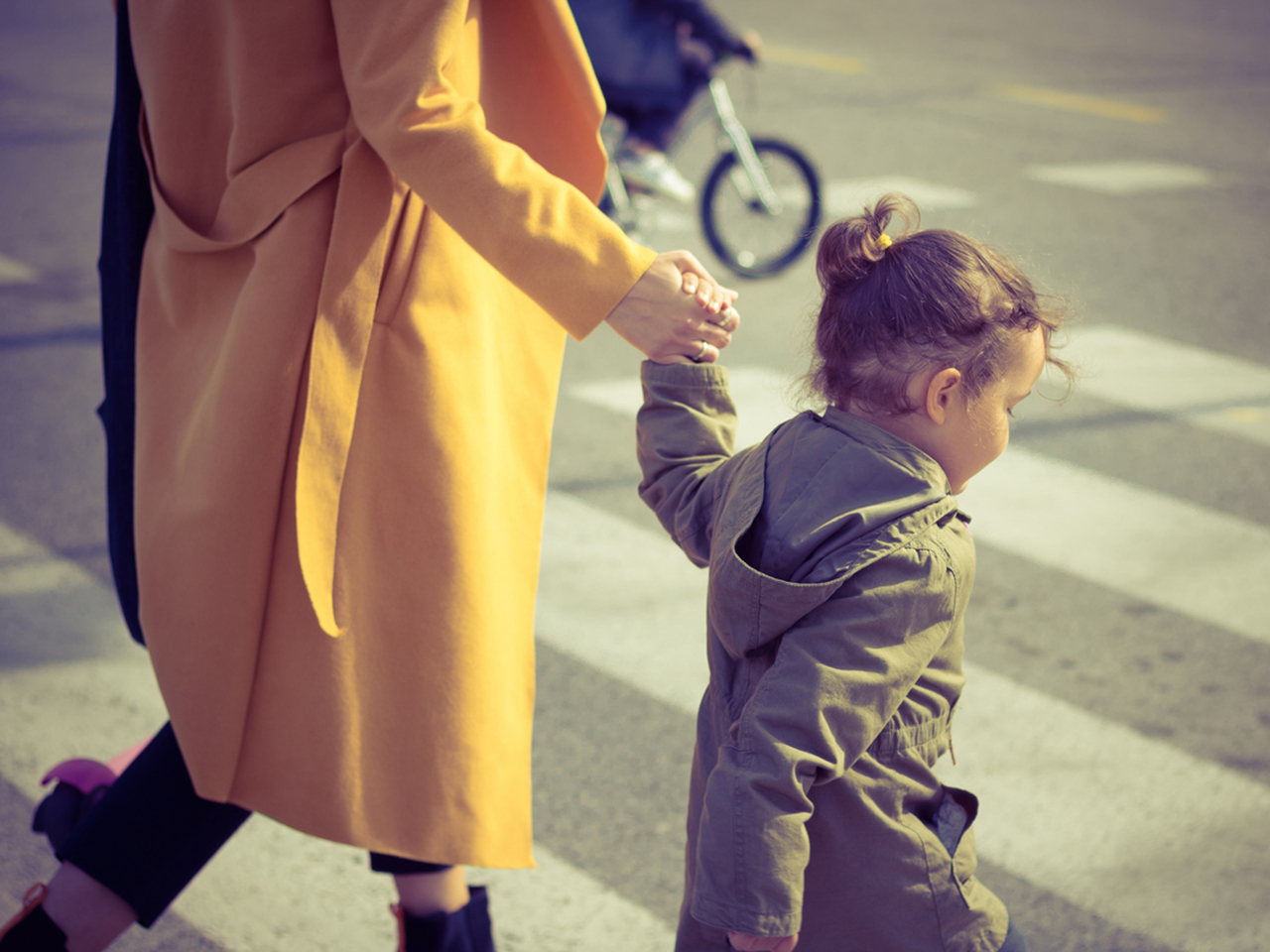 Small girl holding mother's hand while crossing the street at a crosswalk