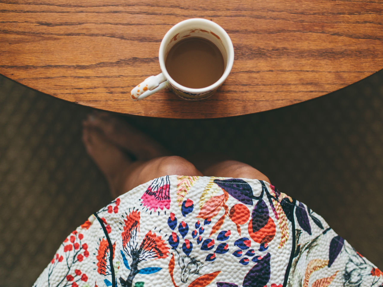 A woman sitting at a table with a cup of coffee in front of her