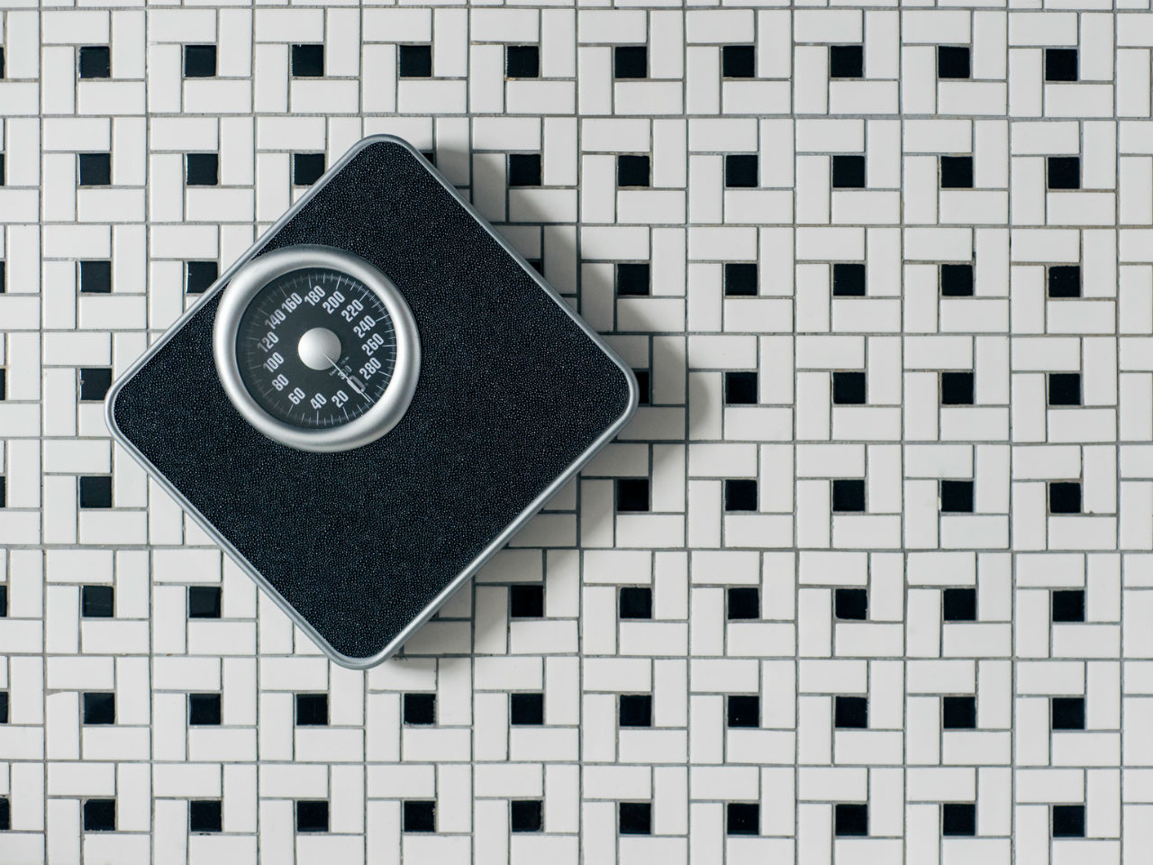 A weighing scale on a tiled floor