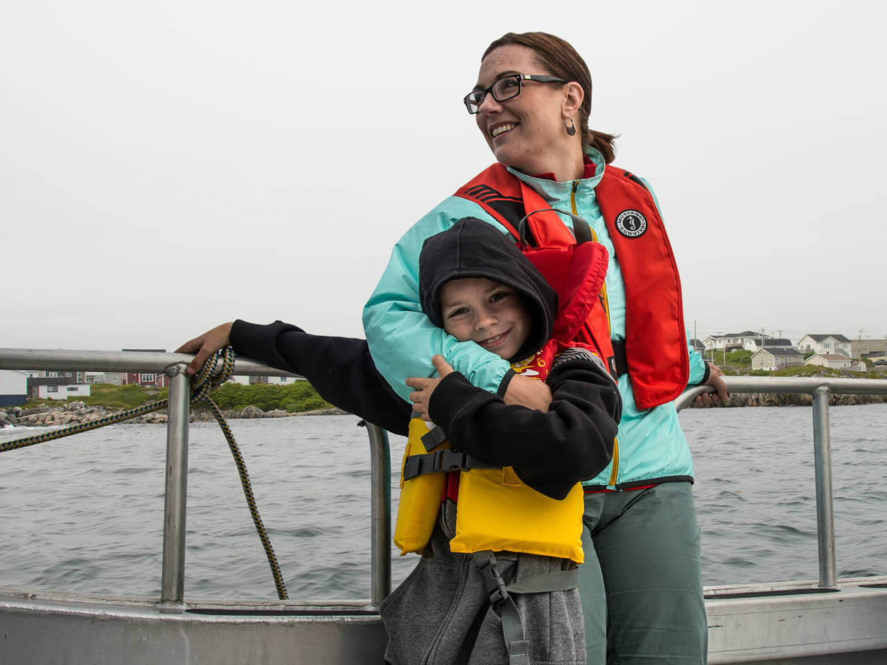 A woman hugging a young boy while riding a boat on the lake