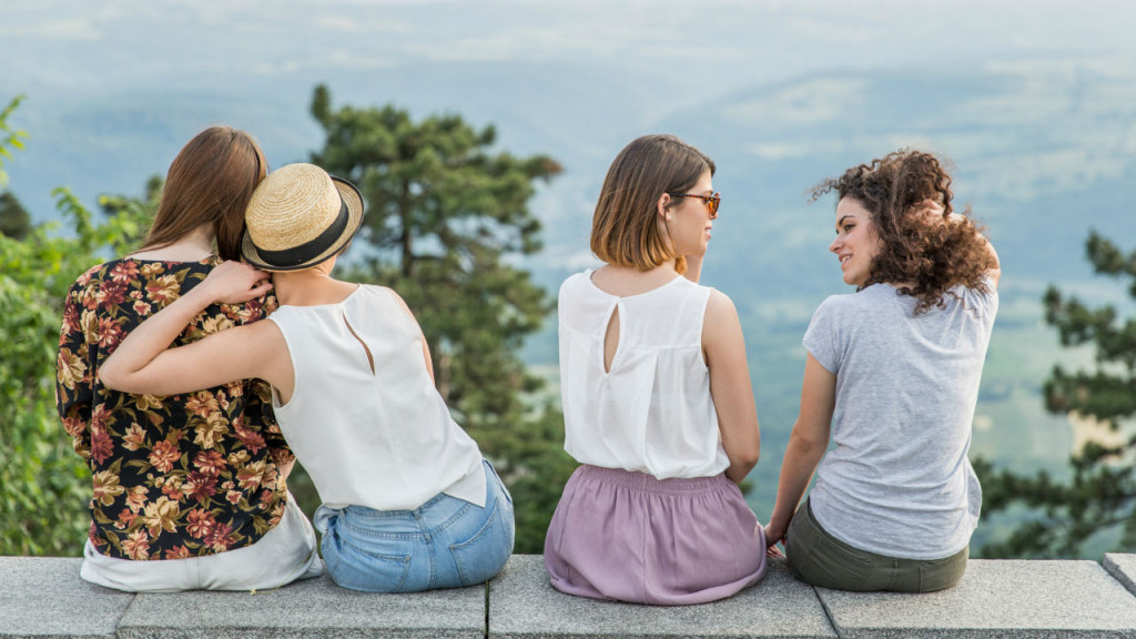 Four young women sitting together with their backs facing the camera