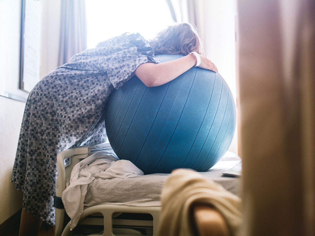 A woman in lobourwith contractions prepares to give birth in a clean white hospital setting. She leans on a birthing or fitness ball to ease the intensity of her contractions.